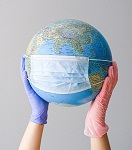 Hands with latex gloves holding a globe with face mask. Photo by Anna Shvets from Pexels